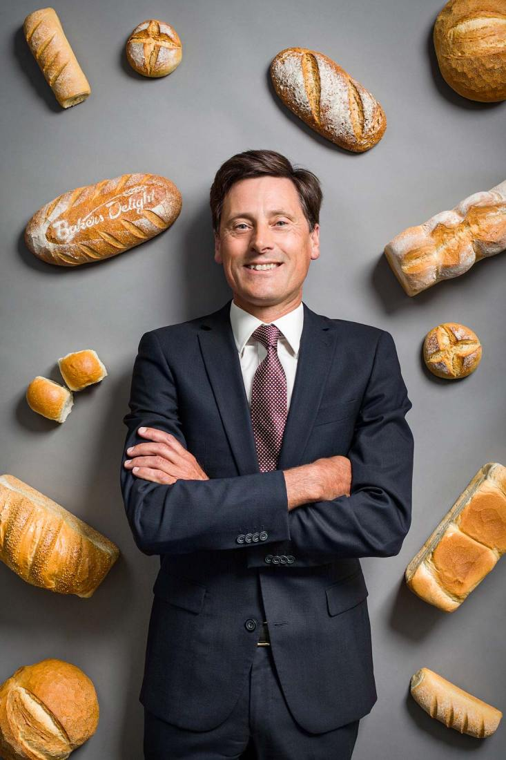 Creative and conceptual portrait of Baker's Delight director Chris Gurney surrounded by bread, which was used as the cover image for the magazine.