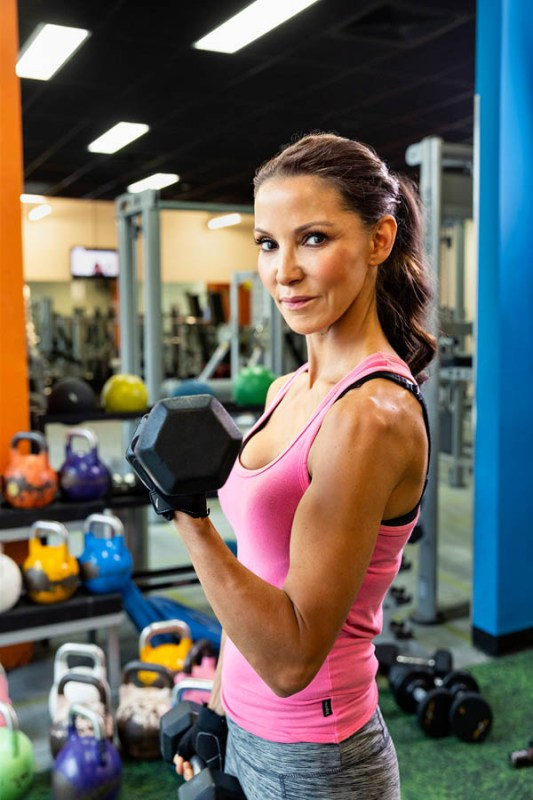 Woman in a gym holding a dumbell