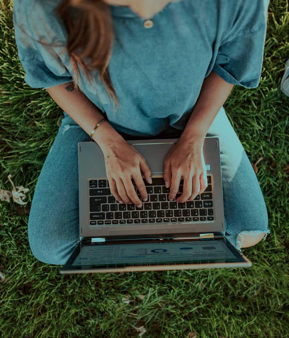 Lovely girl on her laptop sitting on the grass