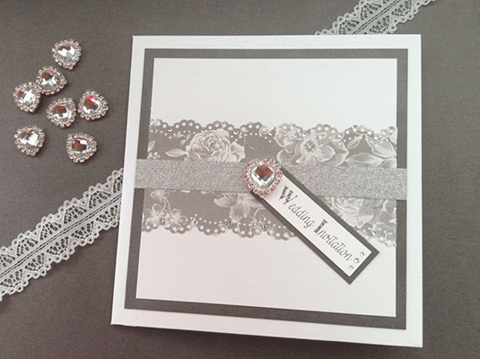 Pretty grey and white flowery wedding invitation with heart detail. Shabby chic vintage wedding stationery
