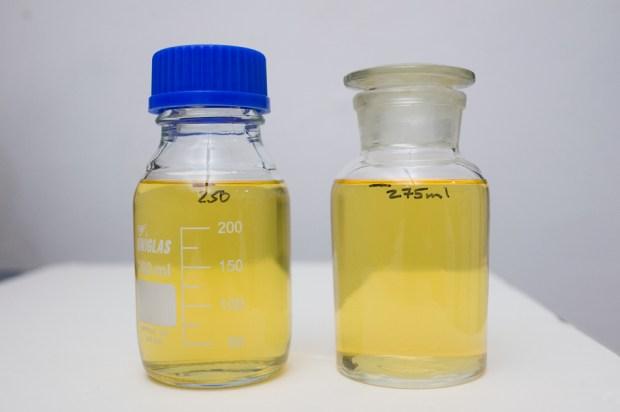 Depois da filtragem. A garrafa da esquerda tem só a mistura de Goma Sandaraca e álcool. A da direita tem adicionado o Óleo de Lavanda, que depois de bem misturado, não muda a aparência da solução.