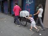 Lucio e seu filho levando a bicicleta de equipamentos