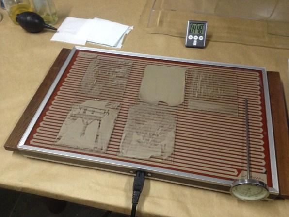Imagens envernizadas sendo secadas em placa quente