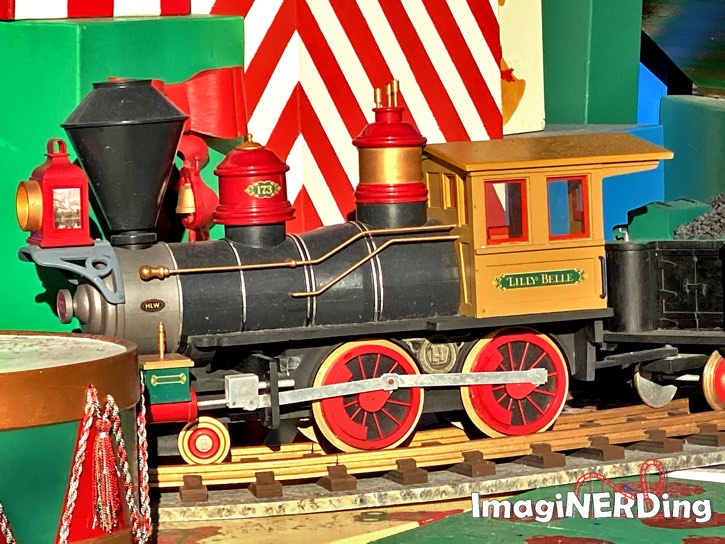 close-up of the lilly blue toy engine under the main street christmas tree at the magic kingdom
