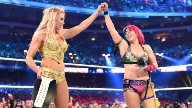 Asuka raises Charlotte Flair's hand