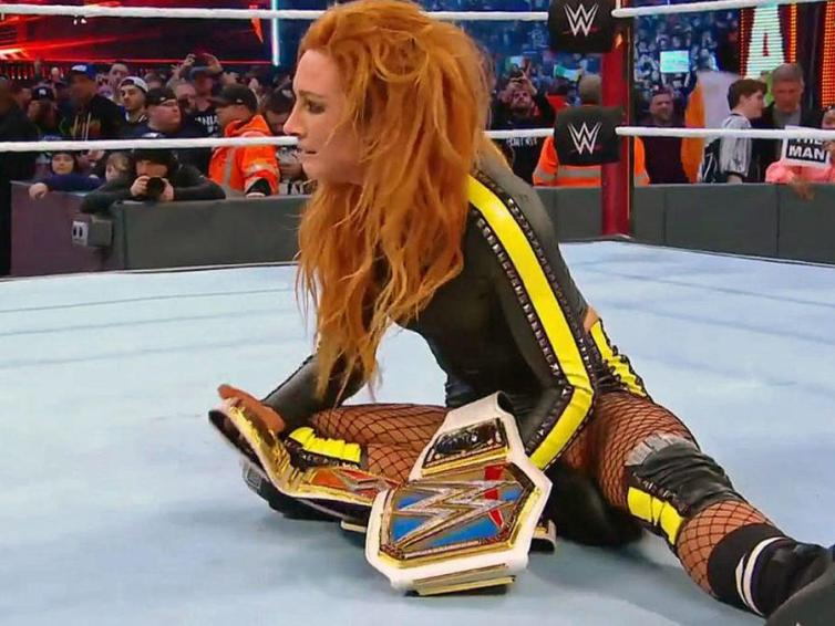 Becky Lynch holds her two championships at Wrestlemania 35