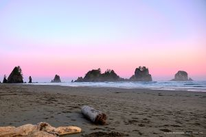A pink sky behind sea stacks on a beach near the Pacific Ocean