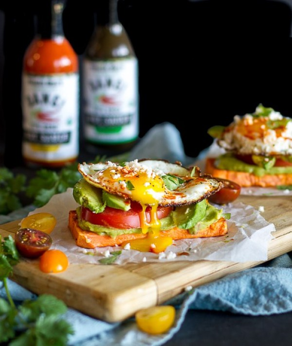 Layered Sweet Potato Toast Stacks - topped with avocado, tomato, egg and hot sauce!