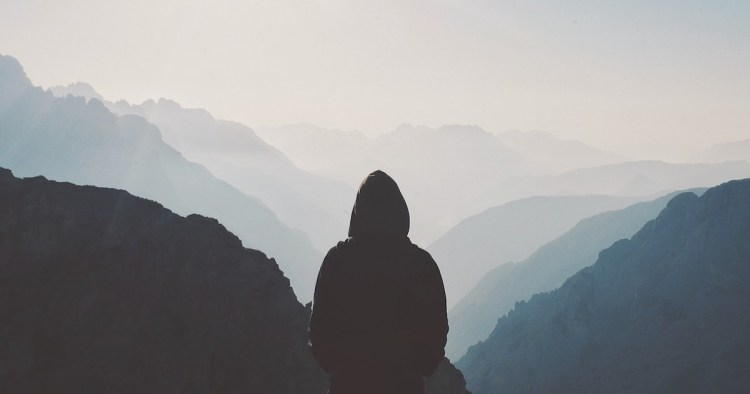 man overlooking grey foggy sky in rolling mountains