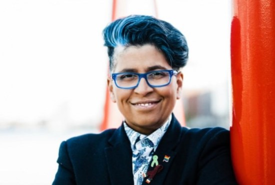 Dil Wickremasinghe standing by a red structure, wearing blue glasses, she is a leading LGBT+ radio broadcaster honoured on World Radio Day