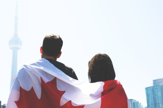 Un drapeau du Canada sur le dos d'un couple de dos regardant la CN Tower de Toronto