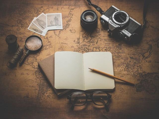 Un carnet de voyage ouvert et vide posé sur un vieux mappemonde marron. Entouré par une vieille loupe, de vieilles cartes postales, des lunettes et un appareil photo.