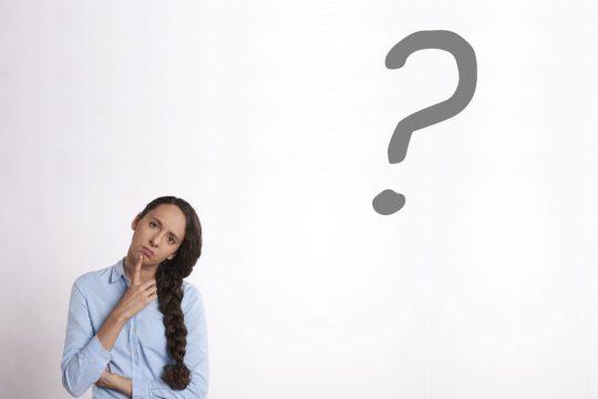 Une personne avec le doigt sur le menton et un point d'interrogation sur un mur blanc.