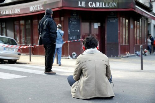 A woman sits outside of the Carillon bar in the 10th district of Paris on November 14, 2015, following a series of attacks in and around the city, leaving at least 120 people killed. Le Petit Cambodge, adjacent to the Carillon bar, was the scene of another attack, which killed at least 12 people. The assailants struck at least six different venues, ranging from the Stade de France football stadium to a pizzeria. AFP PHOTO / KENZO TRIBOUILLARD