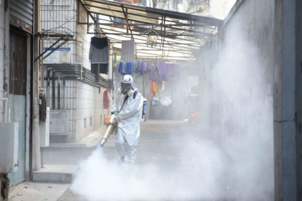 A volunteer sprays disinfectant in Changsha, Hunan province [image: Alamy]
