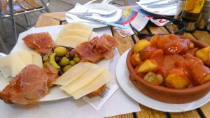 Patatas bravas with cheese and Serrano ham from Guinness House