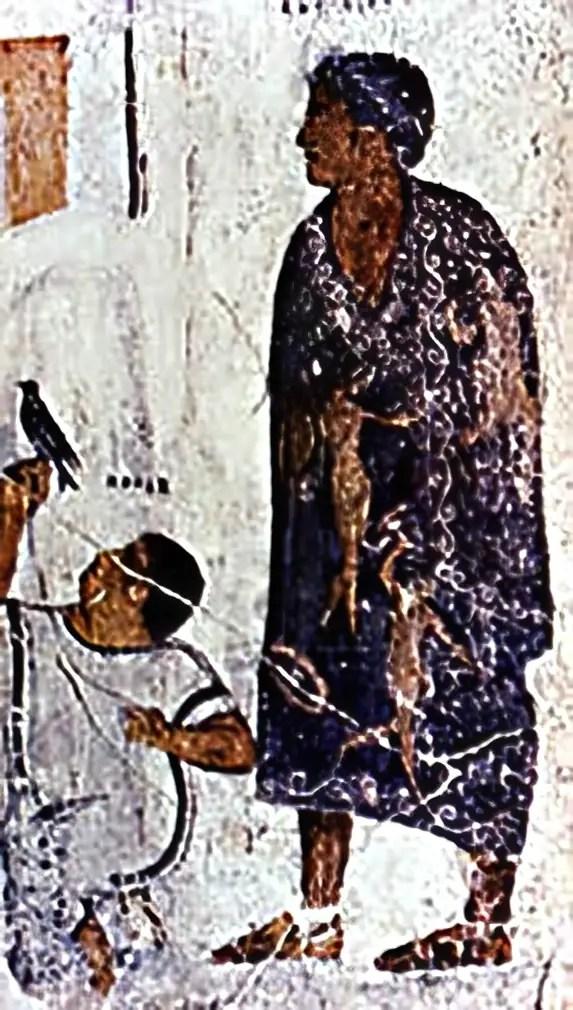 Una toga picta en todo su esplendor. Podemos ver el distintivo color purpura resaltar sobre la imagen y los tonos dorados de los adornos (figuras de héroes al estilo griego) darle un semblante especial.