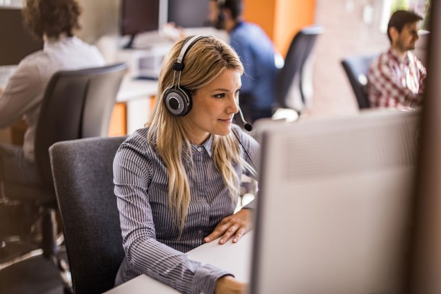 woman hearing microphone headset in sitting at computer desk