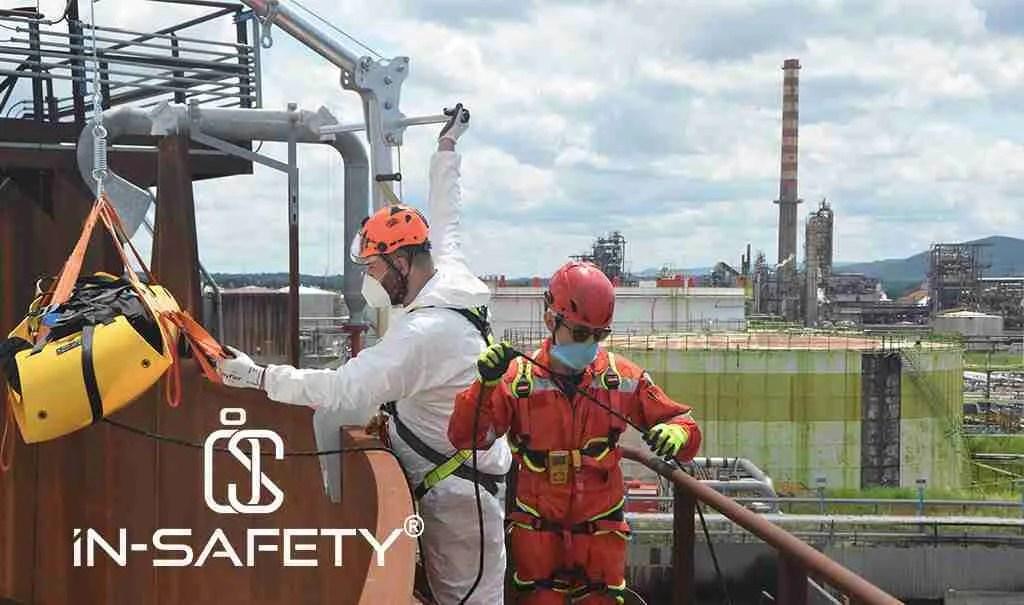 Operatori in tuta, elmetto e DPI eseguono delle prove di recupero e salvataggio da un serbatoio atmosferico a tetto galleggiante durante la fermata impianti in una raffineria