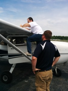 Preflight checklist!  I think he's checking the gas tank.