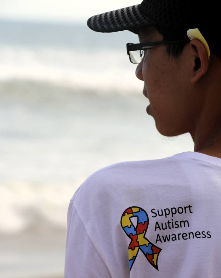 young man wearing a Support Autism Awareness t-shirt at the beach