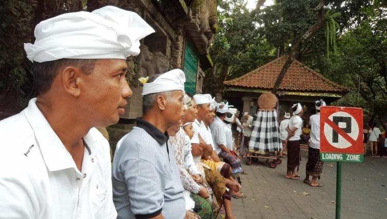 Ubud men waiting for to join parade of masks. Photo via Geoff Vivian