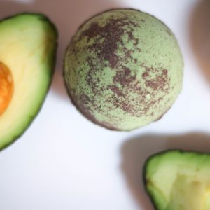 a green and brown bath bomb with avacados around
