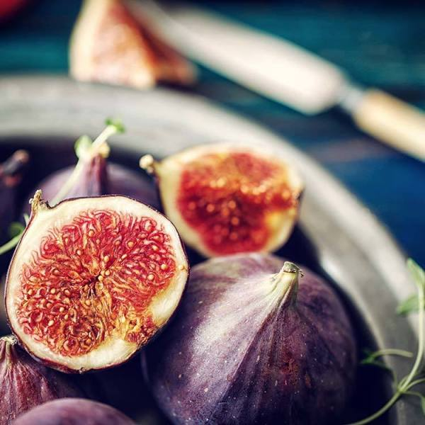 figs on a plate some cut in half revealing the red flesh of the fig