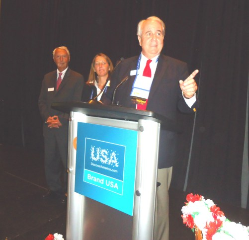 Gesturing to acknowledge someone in the audience, Mike Gallgher, co-founder and co-chairman of City Pass addresses a jam-packed crowd of journalists and suppliers at the conclusion of the CityPASS-sponsored Media Marketplace reception. Joining Gallagher are Mike Morey, his fellow co-founder and co-chairman, and Megan Allen, the company's president and CEO.
