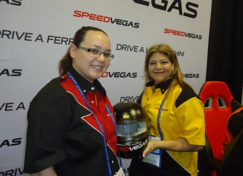 At the SPEEDVEGAS booth, Allison Raskansky (right), senior vice president, business development and Diane Roehr, sales coordinator, hold the headgear that is required for those who are going to drive one of the company's many luxury racing autos.