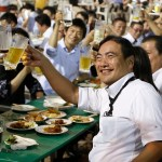 A group of Tokyo businessmen and businesswomen toast with mugs of beer at a beer garden at the rooftop of Nihonbashi-Mitsukoshi department store in Tokyo