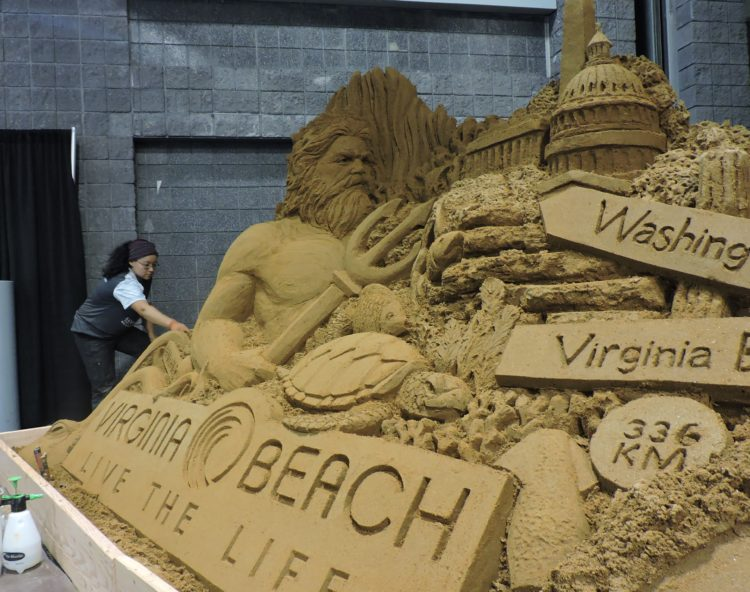 Sue McGrew, artist and sculptor with Treasure Island-based Standing Ovation, puts the final touches on the Virginia Beach CVB sand sculpture located at one of the main entrances to IPW.