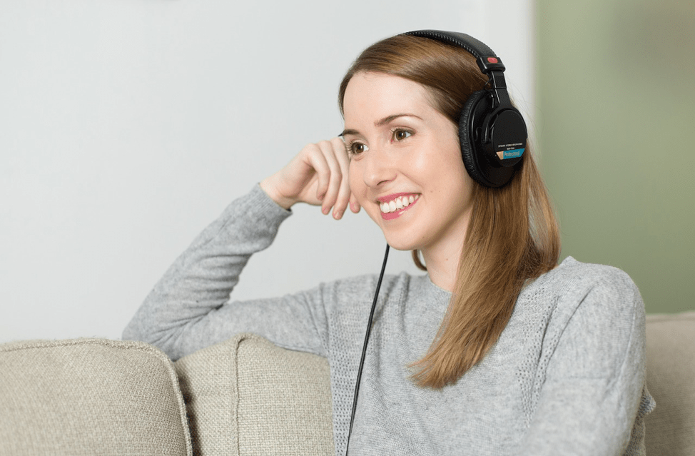 Photo of a lady on a sofa with headphones