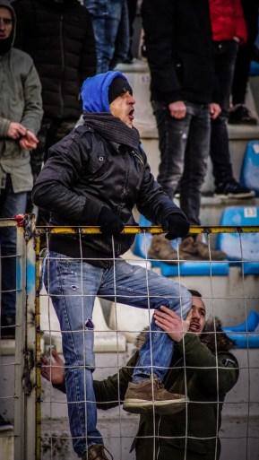 Supporter van Partizani in de hekken