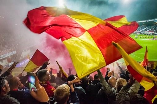 Het Goffertstadion, NEC-Go Ahead Eagles. Op de foto staan alle ingrediënten voor een goed uitvak. De vlaggen, wat pyro, een biertje, de onvermijdelijke telefoons en vrijwel geen zicht op het veld.