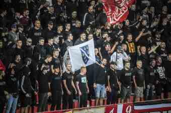 Supporters van Velez Mostar tonen een vlag met embleem van het Bosnische leger.