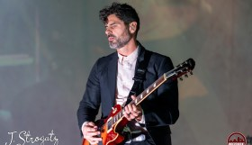Musician Tycho playing guitar while performing at Franklin Music Hall