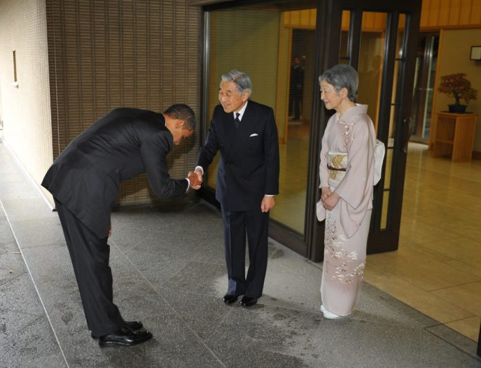 """US President Barack Obama (L) bows as he shakes hands with Japanese Emperor Akihito (C) and as Empress Michiko (R) looks on upon Obama's arrival at the Imperial Palace in Tokyo on November 14, 2009. Billing himself America's first """"Pacific president"""", Barack Obama on November 14 said the United States did not seek to """"contain"""" China and promised a full US role in charting Asia's future. AFP PHOTO/Mandel NGAN (Photo credit should read MANDEL NGAN/AFP/Getty Images)"""