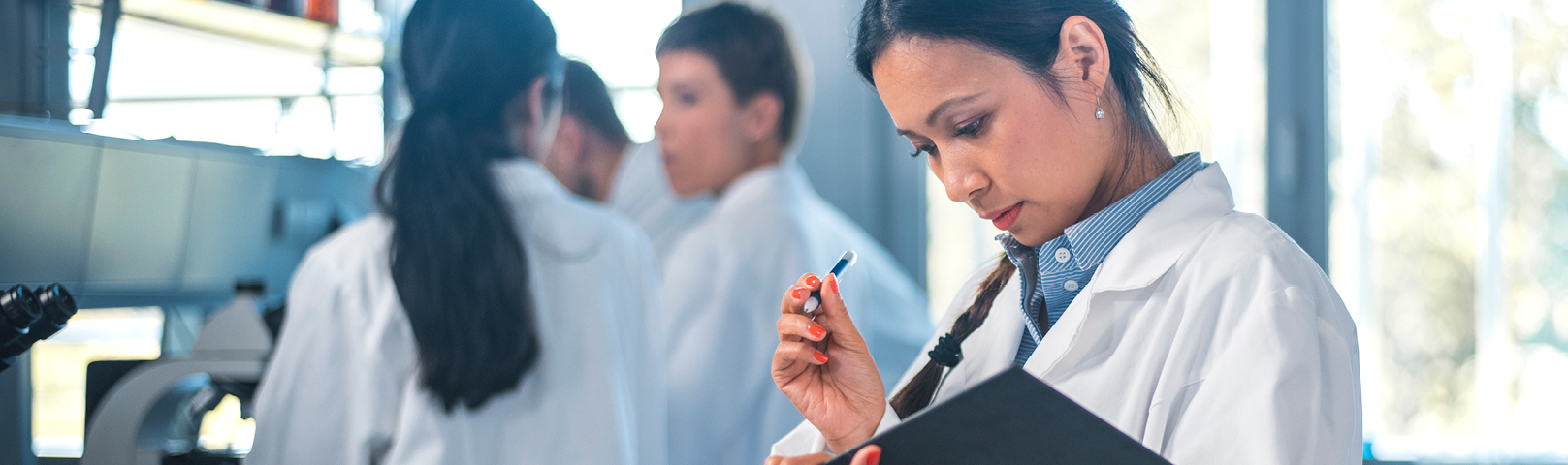 a latino woman in a lab coat reviews her clip board carefully just next to a microscope in a lab