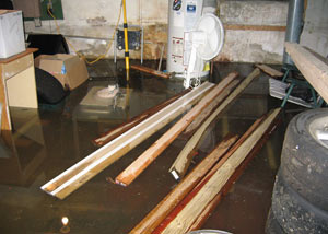 A severely flooding basement in Carmel, with lumber and personal items floating in a foot of water