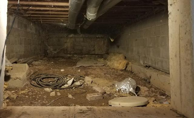 Crawl space filled with debris and dirt