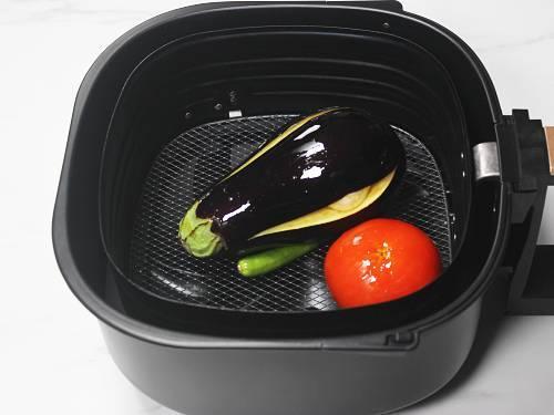 eggplants garlic tomatoes chilies in air fryer basket