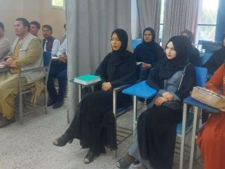 Male and female students are segregated in the classroom by grey fabric curtains