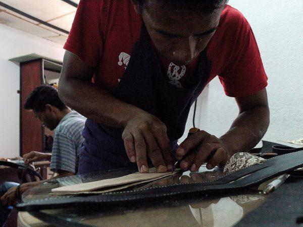 Un des ouvriers de l'atelier I Z A H O travaille sur la sangle de Poun.