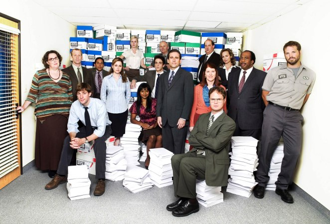 The characters of The Office all sat in a room, some sat on stacks of paper