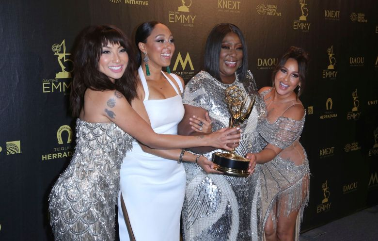 "Jeannie Mai, Tamera Mowry-Housley, Loni Love, Adrienne Houghton. Jeannie Mai, from left, Tamera Mowry-Housley, Loni Love, and Adrienne Houghton pose in the press room with the award for outstanding entertainment talk show host for ""The Real"" at the 45th annual Daytime Emmy Awards at the Pasadena Civic Center, in Pasadena, Calif45th Annual Daytime Emmy Awards - Press Room, Pasadena, USA - 29 Apr 2018"