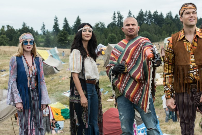 "DC's Legends of Tomorrow -- ""The Virgin Gary"" -- Image Number: LGN401b_0382b.jpg -- Pictured (L-R): Caity Lotz as Sara Lance/White Canary, Tala Ashe as Zari, Dominic Purcell as Mick Rory/Heat Wave and Nick Zano as Nate Heywood/Steel -- Photo: Dean Buscher/The CW -- © 2018 The CW Network, LLC. All Rights Reserved."