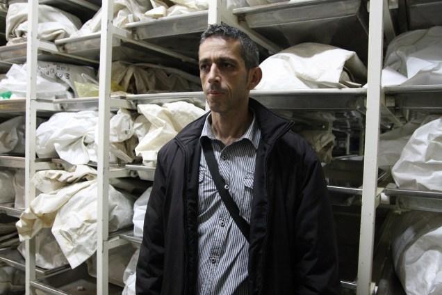 Nedim Durakovic del Komemorativni Centar di Tuzla. Alle sue spalle un dettaglio del magazzino in cui sono conservati i resti esumati delle vittime bosniache