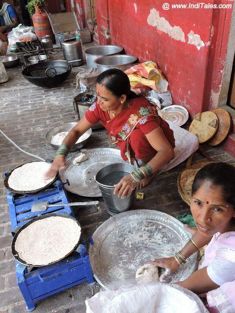 धर्मशाला में अपना खाना पकाते तीर्थ यात्री