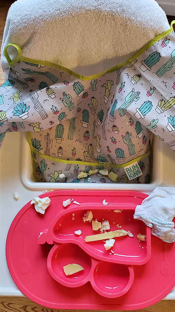 A sleeved bib used to feed baby.